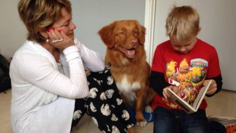 På Linnéuniversitetet i Växjö utbildas bokhundar som sitter och lyssnar när barn lär sig läsa högt. Kulturminister Lena Adelsohn Liljeroth (till vänster) lyssnar tillsammans med hunden Lootah på när Melker Sebelius Nilsson läser. Foto: Catharina Henriksson