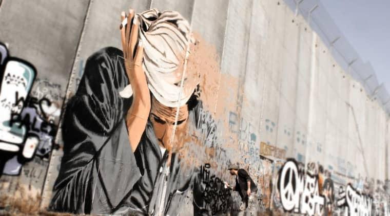Gränsöverskridande graffiti. En jordansk beduin evigt försänkt i en gest av oändlig trötthet målad av Shai Dahan på den åtta meter höga mur som skiljer palestinier från israeler på Västbanken. Foto: Borås konstmuseum
