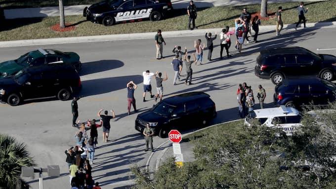 Studenter på skolan håller hand, när de evakueras efter skjutningen. Foto: MIKE STOCKER / AP TT NYHETSBYRÅN