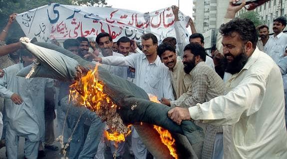 Uppretade pakistanier bränner en docka föreställande Fredrik Reinfeldt. Protesterna gäller Lars Vilks teckning av profeten Muhammed som rondellhund i Nerikes Allehanda tidigare i somras. Foto: Tabassum Rizwan