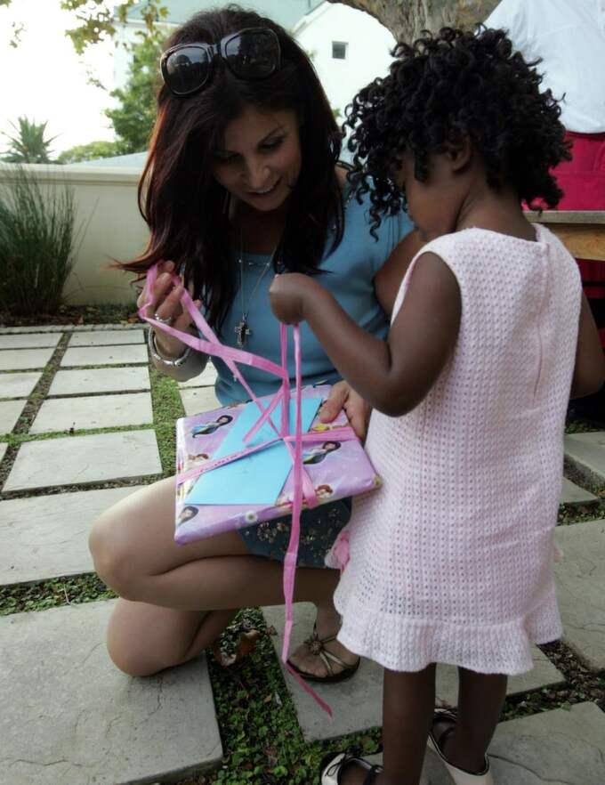 PRESENTÖPPNING. Lilla Zoe får hjälp av sin nya mammam Carola att öppna paketet som innhöll en sagoboksversion av Bibeln. Foto: Torbjörn Selander