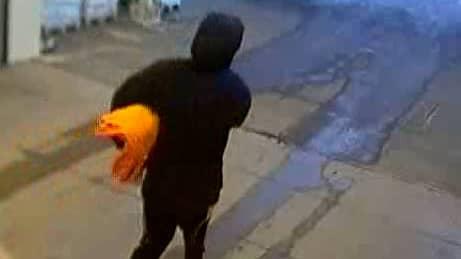 Mannen på väg ut med säcken under armen. Foto: Polisen