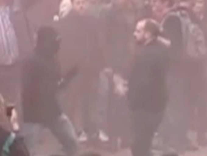 Hannes Lundholm, 33, till höger i bild, blir arg när en grupp maskerade aktivister försöker tränga igenom polisens barrikad. Han ger dem fingret och frågar vad de håller på med