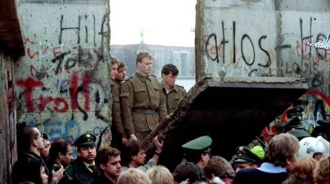 PORTEN TILL FRIHETEN. Östtyska vakter ser genom den rivna Berlinmuren den 11 november 1989. Foto: Lionel Cironneau / AP SCANPIX SWEDEN