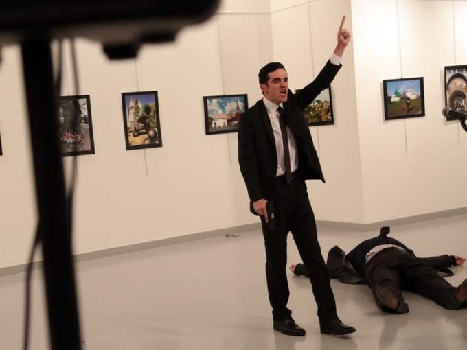 """""""En man i en svart kostym stod bakom ambassadören, som vi trodde var där som skydd. Sedan sköt han upp i luften, och sköt sedan ambassadören"""", säger en fotograf som var på plats. Ambassadören Andrei Karlov dödförklarades senare på sjukhus. Foto: Burhan Ozbilici / AP TT NYHETSBYRÅN"""