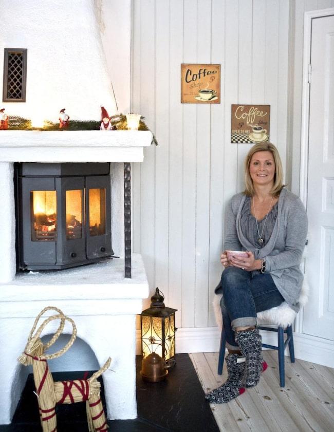 """Här bor: Louise Karlsson med sin son.  Huset: 6 rum o kök, ca: 185 kvm, ¼ del av ett stort kaptenshus. Byggår: 1790<br>Louise myser vid den öppna spisen, som är uppmurad efter egen design. Ny fast i gammal stil. På fötterna har hon långa sockor från """"Odd-Molly"""".<br>"""