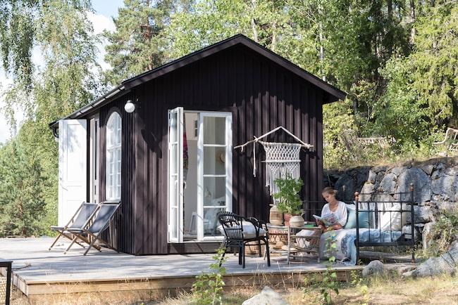 Uteplatsen är parets favoritplats och har inretts med en gammal järnsäng, ett begagnat rottingbord och Ikeas svarta fåtöljer. Fasaden målades med svart Falurödfärg.