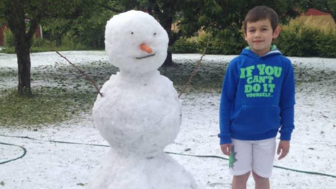 """David, 8, och pappa Göran passade på att bygga en snögubbe efter hagelovädret. """"Det kändes lite bisarrt att bygga snögubbe och samtidigt ha på sig sommarshortsen,"""" säger Göran. Foto: Privat"""