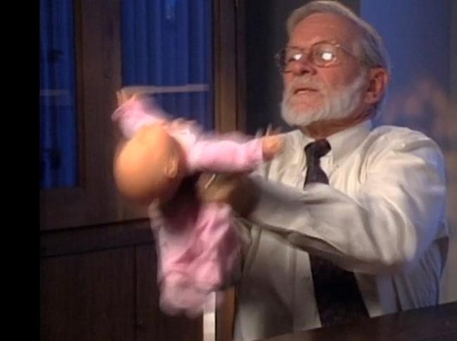 """Bild ur dokumentären """"The Syndrome"""" som granskade skakvåld. Här en bild ur filmen där professor Robert M. Reence, en av förespråkarna, demonstrerar hur skakning av barn går till på en docka."""