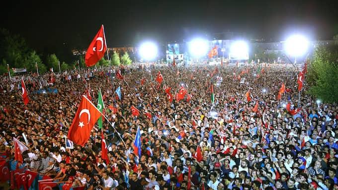 Människor i Ankara viftar med flaggor vid en minnesceremony för förra årets kuppförsök, där 249 personer dog. Foto: PRESIDENTIAL PRESS OFFICE HANDOUT / EPA / TT / EPA TT NYHETSBYRÅN