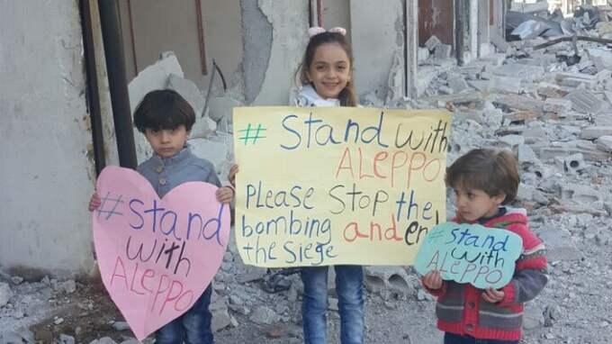 """Snälla stoppa bombningarna"""" står det på barnens skylt som de håller upp i det sönderbombade Aleppo."""