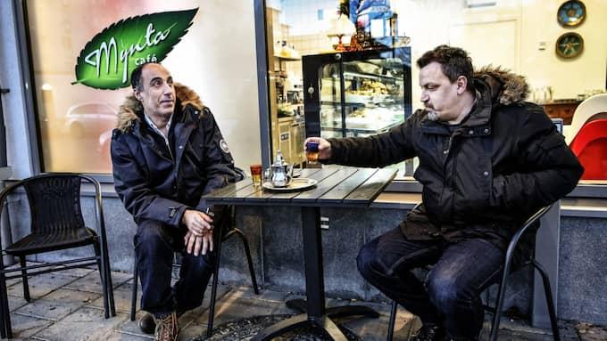 """Wazeer El Goul (till vänster) och Montaser Saqfalhait värmer sig med te. """"När någon blir skjuten här så får det enorm uppmärksamhet och det kommer journalister från andra länder, varför skriver ni inte lika mycket när det händer i stan?"""" frågar Wazeer El Goul. Foto: Alex Ljungdahl"""