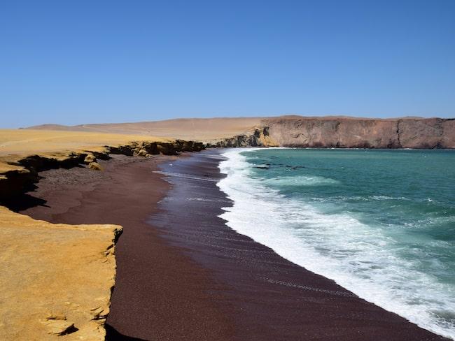 Ockragul öken möter roströd strand möter kristallklart turkosblått hav.