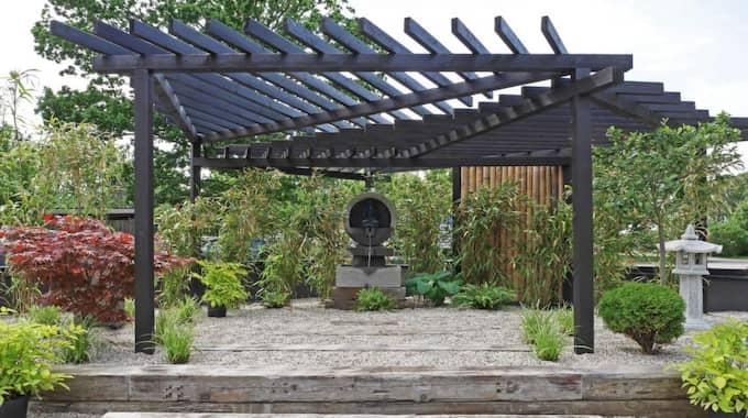 En japansk trädgård har ofta en tydlig entré. Här byggde de en grandios portal av bjälkar i lärkträ som sedan betsades mörka och behandlades med träolja.