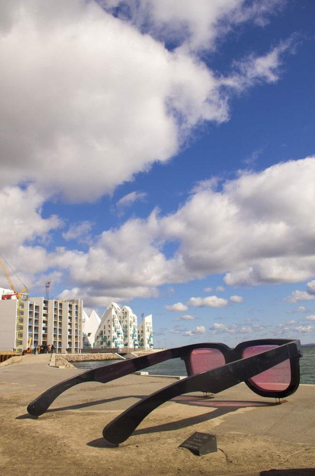 Vartannat år förvandlas stranden söder om Århus till en två kilometer lång konstutställning. Solglasögonen är kvar från förra utställningen och finns nu i nya bostadsområdet Isbjerget.