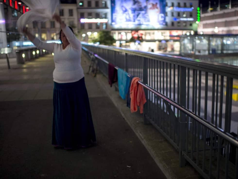 En kvinna tvättar kläder innan det är läggdags vid Sergels torg. I lördags kväll fick en äldre kvinna sina tillhörigheter uppeldade av en man som cyklade förbi. Foto: Meli Petersson Ellafi