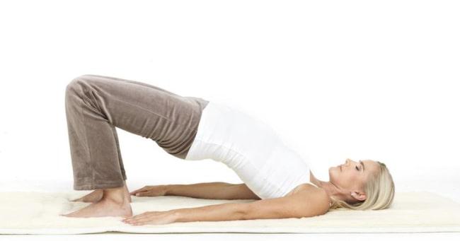 """2 Höftlyft<br>Ligg på rygg. Sätt i fotsulorna och dra hälarna så nära baken som möjligt. Om du når håller du om anklarna, lägg annars handflatorna mot golvet. Lyft baken så högt du kan mot taket samtidigt som du andas in (tänk """"sat""""). Sänk baken ner i golvet igen på utandning (tänk """"nam""""). Fortsätt upp och ner på detta sätt i 2-3 min. Avsluta med ett rotlås i det övre läget. Vila på rygg 1-2 min. OBS: Denna övning kan göras innan mens, men inte de dagar du har mens."""