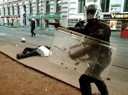 """UTSATT YRKE. En demonstrant har kastat en gatsten i huvudet på en kravallpolis. Kollegan drar sitt vapen. """"När ungdomar kastar sten och brandbomber på poliser och brandmän så är det många som undrar varför. Men när polismän uttalar sig förkastligt är det inga experter som vill analysera"""", skriver Hasse Brontén som är före detta polis. Foto: LARSERIC LINDÉN"""