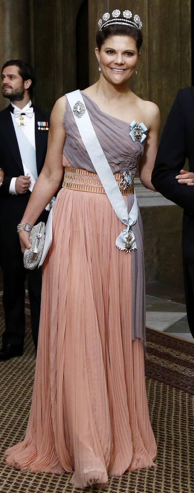 KRONPRINSESSAN VICTORIA – Grått går riktigt bra till den persikofärgade kjolen och Victoria toppar stilen på bästa sätt med en silverfärgad väska. Klänningen har dessutom en fint markerad midja som är smickrande för figuren. Foto: Patrik C Österberg All Over Pre