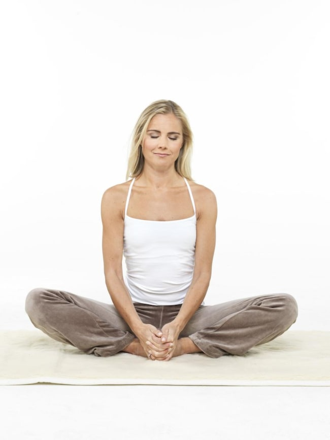 """<strong>1 Fjärilen</strong><br>Sitt med rak rygg. För ihop fotsulorna mot varandra framför dig. Håll om fötterna och dra dem så nära in mot kroppen som möjligt. Med slutna ögon flexar du knäna upp och ner, mjuka lätta rörelser, som fjärilsvingar. Andas lugna djupa andetag in och ut genom näsan genom hela övningen. Tänk """"sat"""" på in- och """"nam"""" på utandning. 2-3 minuter. Avsluta med ryggen rak och ett rotlås. Vila 1-2 min."""