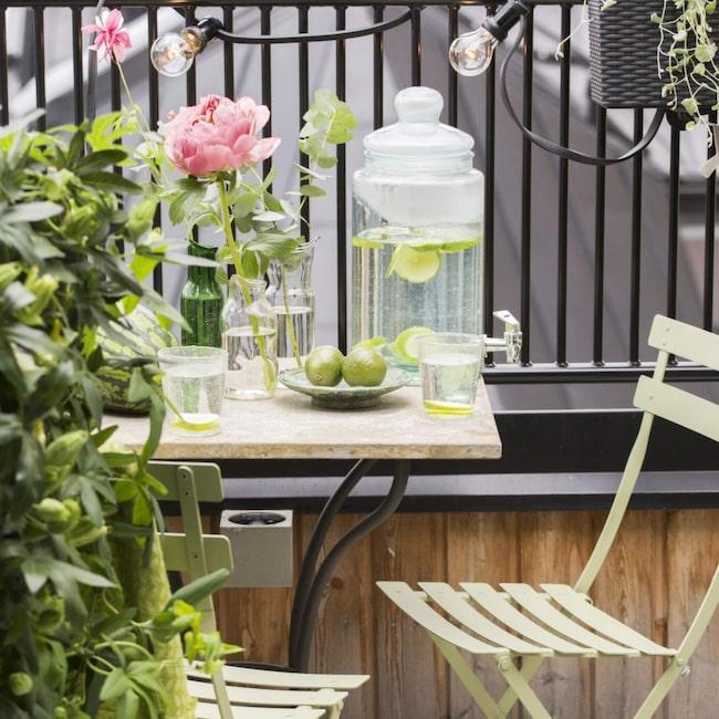 På en liten balkong passar ett fint kafébord med stolar bra. Inred med mycket gröna växter och ljusslingor – så får du en härlig stund.