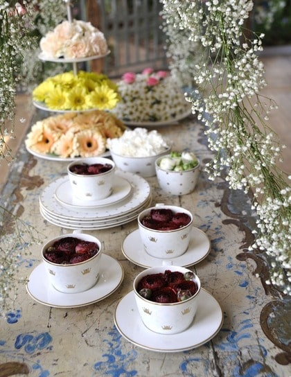 Fikastund. Kaffet är upphällt. Ranunkler i kopparna, som hör till den officiella bröllopsservisen från Rörstrand. På tårtfatet ligger det visst några frestande mazariner – eller är det gerbera? Svårt att säga. Alltihop är inramat av den skira brudslöjan.