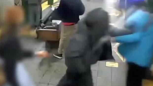 Här knuffas mannen ner på tunnelbanespåret