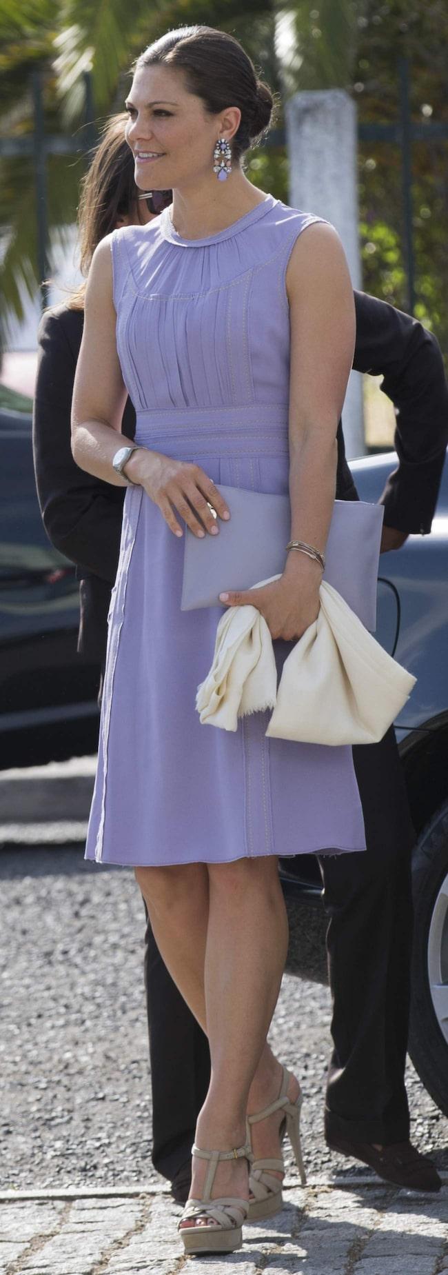 """<a href=""""http://www.expressen.se/mode/kronprinsessan-victoria---stilguide/"""">Kronprinsessan Victoria </a>i Portugal iklädd lavendelfärgad knäkort klänning och matchande kuvertväska och örhängen."""