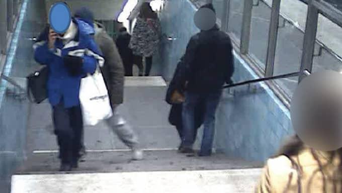 Mannen smyger upp bakom den äldre kvinnan som pratar i telefon. Foto: Polisen