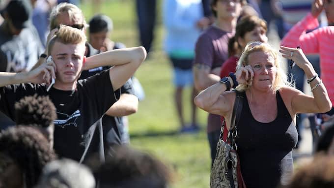 Anhöriga till eleverna väntar oroligt utanför skolan och håller kontakten via telefon. Foto: AMY BETH BENNETT / AP TT NYHETSBYRÅN