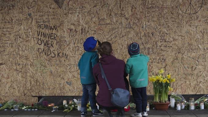 MINNESPLATS. En mamma och två barn vid väggen som satts upp över hålet där lastbilen körde in i Åhléns i Stockholm. Foto: REX/SHUTTERSTOCK