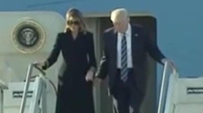 När presidentparet går av planet försöker Donald Trump ta hustruns hand...