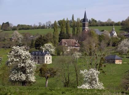 Pampiga herrgårdar i korsvirke, charmiga bondgårdar och små slott brer ut sig  på det böljande, gröna landskapet i Normandie.