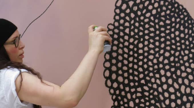 Carolina Falkholt målar det tillfälliga konstverket Sociation på en vägg i Kristinehamns konstmuseum. Foto: Privat